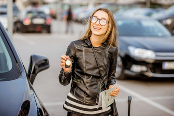 Portrait of a young happy woman with keys and rental contract standing near the car on the outdoor parking