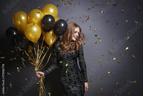 Joyful woman with bunch of balloons