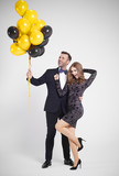 Man with bunch of balloons embracing woman - 178085906