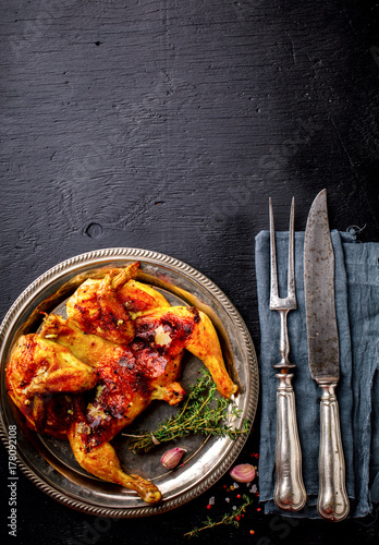 Grilled fried roast Chicken Tabaka with thyme and garlic, in Frying pan on wooden Background Poster