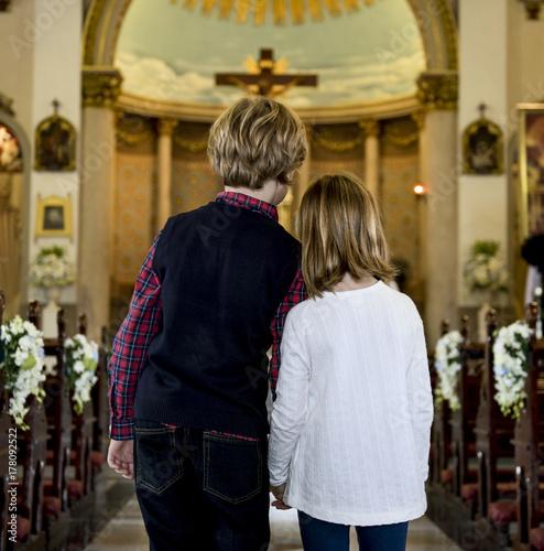 Children praying together inside a church Poster