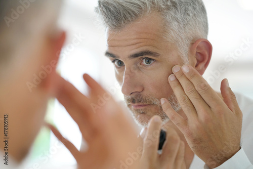 Leinwanddruck Bild Middle-aged man applying cosmetic on his face, mirror view