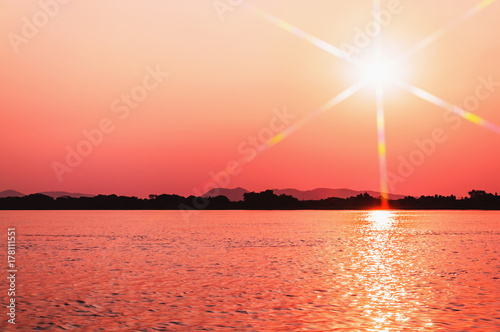 Foto op Plexiglas Koraal Amazing sunset at Paraguai river in Pantanal, Brazil. The river and the sun with flares at a golden hour sunset, water reflection and silhouette of nature on background.