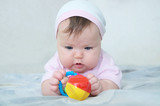 Early brain development. concentrated little baby girl  playing with rattle lying on bed - 178112309