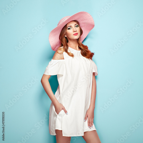 Foto op Canvas Kapsalon Blonde Young Woman in Summer White Dress and Summer Hat. Girl Posing on a Turquoise Background. Hairstyle and Clothing. Fashion Photo