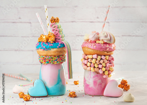 Two Freak Shakes Topping With Donut Marshmallow Popcorn And Marmalade Over Grey Background