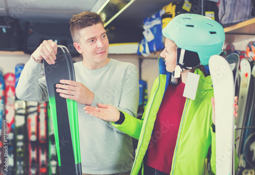 Seller is helping girl in equipment to choose ski
