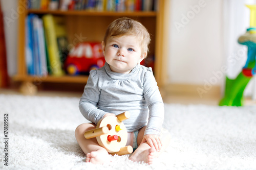 Adorable baby girl playing with educational wooden toy in nursery Poster