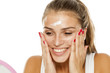 Quadro young woman applying cream to her face