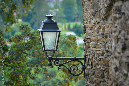 Old metal street lantern on a medieval fortification's wall