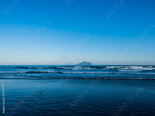 The peaceful black sand beach with the little incoming waves toward shore Poster