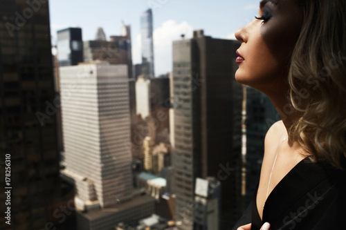 Sexy woman in black silk robe stands with naked shoulders before a panoramic win Poster