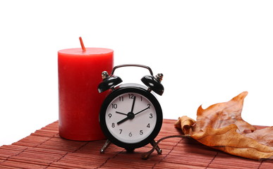 Red candle, small clock and dry leaf on isolated on white background