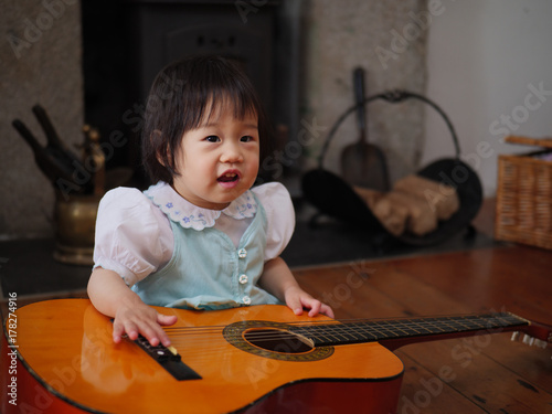 baby girl play guitar at home Poster