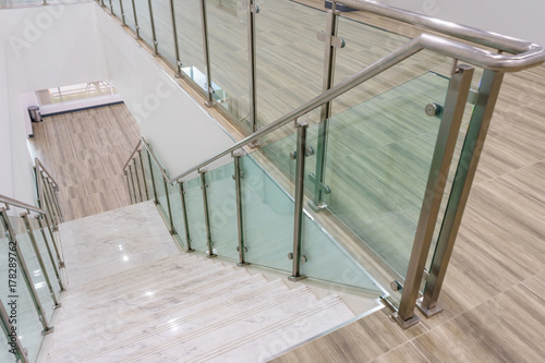 Modern white marble stairs with steel and glass railing in a new modern building. - 178289762