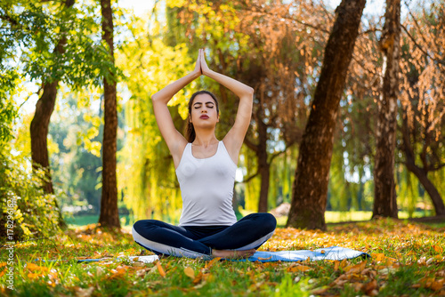 Fototapeta Young beautiful woman practicing yoga in the park.