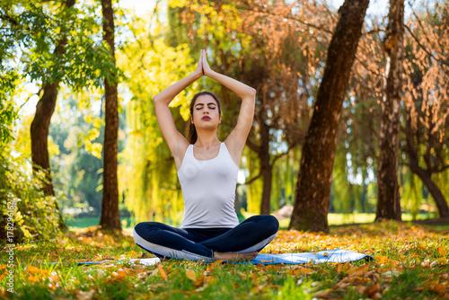 Papiers peints Ecole de Yoga Young beautiful woman practicing yoga in the park.