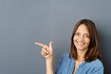 frau zeigt mit dem finger auf etwas und lacht - 178309340
