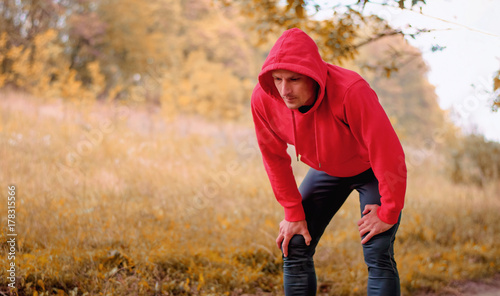 young athletic man in a red sports jacket resting after jogging