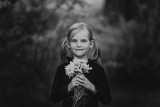 Black and white portrait of a girl with bunches of daisies