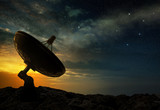 silhouette of a radio telescope at sunset