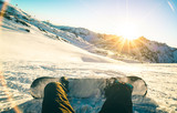 Fototapety Snowboarder sitting at sunset on relax moment in french alps ski resort - Winter sport concept with adventure guy on top of mountain ready to ride down - Legs view point with teal and orange filter