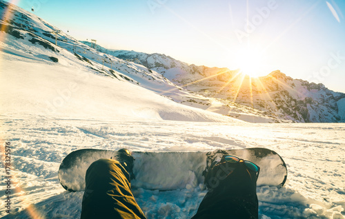 obraz lub plakat Snowboarder sitting at sunset on relax moment in french alps ski resort - Winter sport concept with adventure guy on top of mountain ready to ride down - Legs view point with teal and orange filter