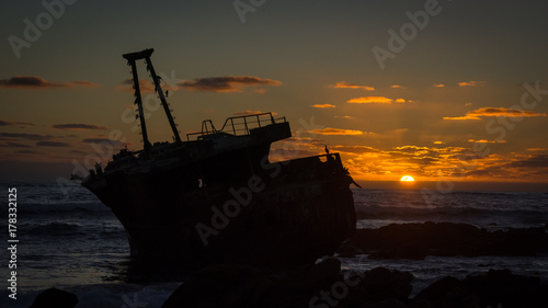 Aluminium Schipbreuk The wreckage of a trawler silhouetted against the setting sun. Cape Agulhas, South Africa.