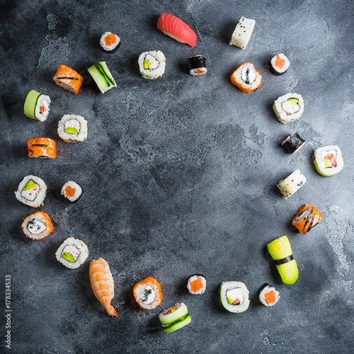 Papiers peints Sushi bar Round frame made of set of Japanese food on dark background. Sushi rolls, nigiri, raw salmon steak, rice and avocado. Flat lay. Top view