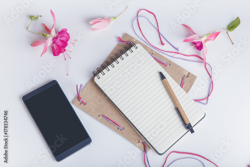 Creative flat lay photo of workspace desk with smartphone, envelope, notepad, pencil, flowers fuchsia with copy space background. Flat lay. © Olga Ionina