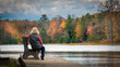 Woman relaxing on a bench in front of colorful autumn foliage at Stony Lake, Stokes State Forest, New Jersey