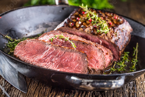 Beef steak. Juicy medium Rib Eye steak slices in pan on wooden board with fork and knife herbs spices and salt - 178343302