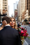 Bride looks over groom's shoulder hugging with him somewhere in New York city