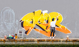 Street artist painting colored graffiti on public space wall - Modern art concept of urban guy performing and preparing live murales paint with yellow aerosol color spray - Cloudy afternoon filter