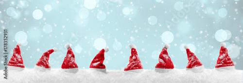 Rote Weihnachtsmützen im Schnee mit winterlichem Bokeh im Hintergrund