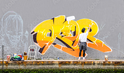 Foto op Plexiglas Graffiti Street artist painting colored graffiti on public space wall - Modern art concept of urban guy performing and preparing live murales paint with yellow aerosol color spray - Cloudy afternoon filter