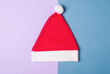 Santa Claus red hat on blue and wiolet paper background , minimal style.