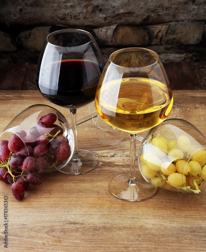 Wineglasses with white grapes and red grapes on wooden background