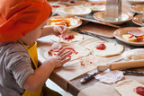 boy making homemade pizza working in the kitchen in chefs uniforms and smear sauce the base - 178370176