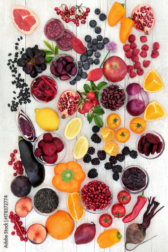 Super food healthy eating concept with health promoting properties of fruit and vegetables high in antioxidants, anthocyanins and vitamins on rustic wood background.