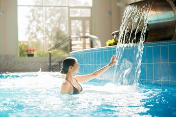 Ecstatic woman touching waterfall while enjoying bathing in swimming-pool of day spa resort © pressmaster