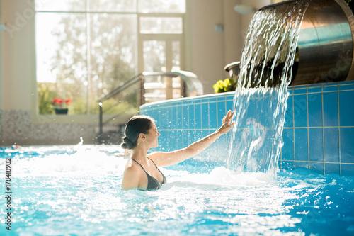 Fotobehang Spa Ecstatic woman touching waterfall while enjoying bathing in swimming-pool of day spa resort