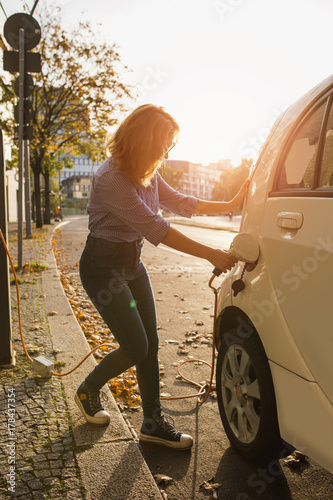 Fotobehang Berlijn Young woman is charging an electric car. The rental car is charging at the charging station for electric vehicles. Car sharing.