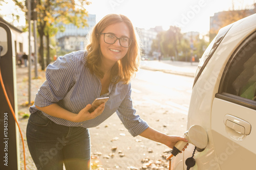 Young woman is standing near the electric car and holding a  smartphone Poster