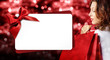 christmas shopping, woman with bag and gift card template on red blurred lights