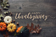 Happy Thanksgiving greeting text with colorful pumpkins, squash and leaves over dark wooden background