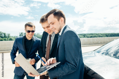 Poster three Businessman Using Digital Tablet Outside against car