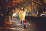 Young woman walking with a dog after shopping