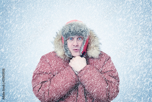 Foto Murales Frozen man in winter clothes warming hands, cold, snow, blizzard