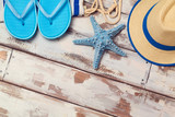 Summer vacation background with flip flops, starfish and hat on wooden board. View from above